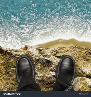 stock-photo-on-the-edge-concept-with-man-standing-on-cliff-ledge-looking-down-at-ocean-191337065